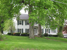 1920s Colonial style home in need of new roof, siding and exterior doors as well as front entrance and chimney work.